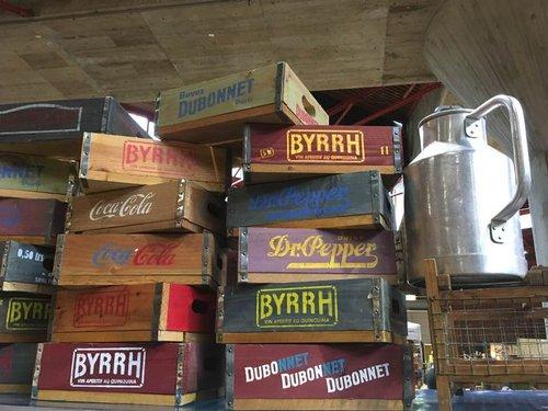 Bouteilles de Coca, DrPepper, Dubonnet et Byrrh encagées